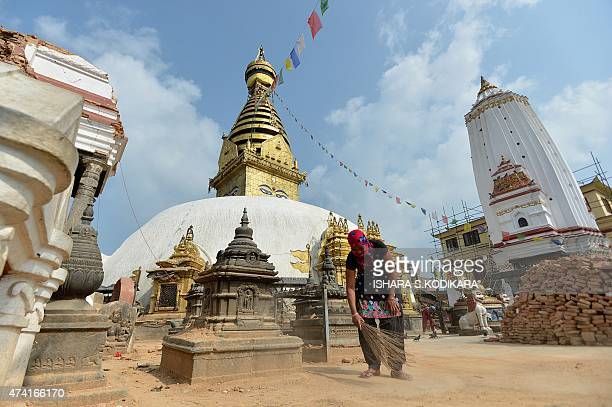 A Nepalese resident sweeps dust from an area of the collapsed Swayambhunath Buddhist temple in Kathmandu on May 21 after multiple earthquakes struck...