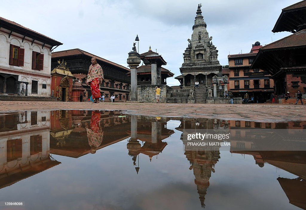 Nepalese residents are reflected in a pool of rainwater in Durbar Square in Bhaktapur some 12 kilometres southeast of Kathmandu on September 21 2011...