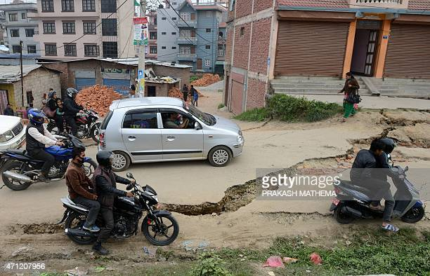 Nepalese residents drive past road damage following an earthquake in Kathmandu on April 26 2015 International aid groups and governments intensified...