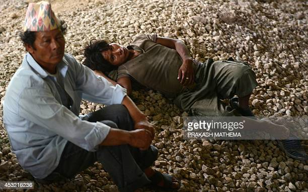 Nepalese residents rest in a governmentrun shelter in the village of Lamo Sanghu by the Sukoshi river some 80 kms northeast of Kathmandu on August 5...