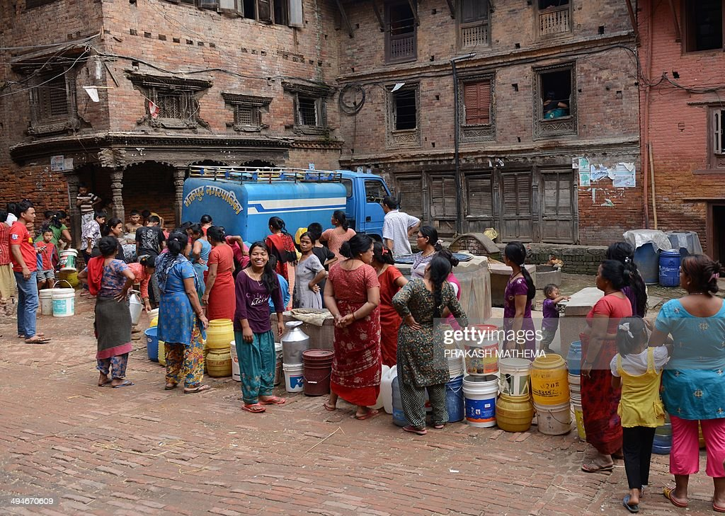 Nepalese residents wait with containers to collect water from a tanker in Bhaktapur, some 12 kilometers south-east of Kathmandu on May on 30, 2014. Residents in the Kathmandu Valley routinely suffer from a shortage of drinking water, and the government water department says that it has managed to supply only one fourth of the total water demand in the city. AFP PHOTO/Prakash MATHEMA
