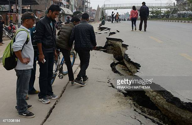 Nepalese residents walk past road damage following an earthquake in Kathmandu on April 26 2015 International aid groups and governments intensified...