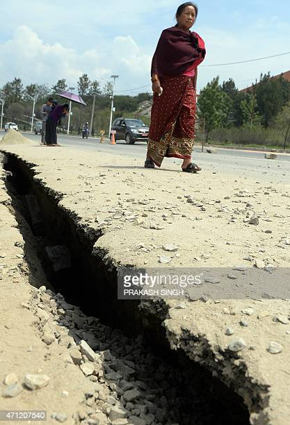 Nepalese residents walks past road damage following an earthquake in Kathmandu on April 26 2015 International aid groups and governments intensified...