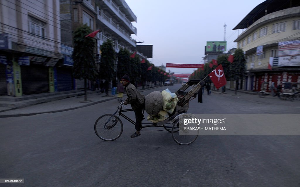 A Nepalese rickshaw with a communist flag crosses a road before attending the inauguration of the Unified Communist Party of Nepal (Maoist) general convention in Hetauda, some 100 km south of Kathmandu on February 2, 2013. Thousands of Nepal's former rebel Maoists are due to gather for their biggest show of strength since taking up arms in a 10-year insurgency and toppling the world's last Hindu monarchy. AFP PHOTO/Prakash MATHEMA