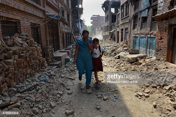 Nepalese schoolgirl Ankita Kapali walks with her mother past damaged buildings to school in Bhaktapur in Bhaktapur on the outskirts of Kathmandu on...