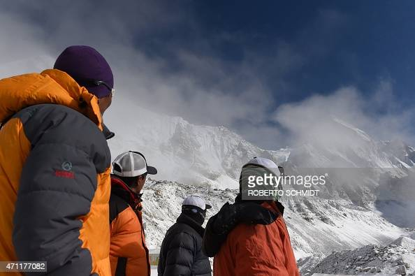 Nepalese Sherpas look up towards an area where an avalanche triggered by an earthquake occurred at Everest Base Camp on April 26 a day after the...
