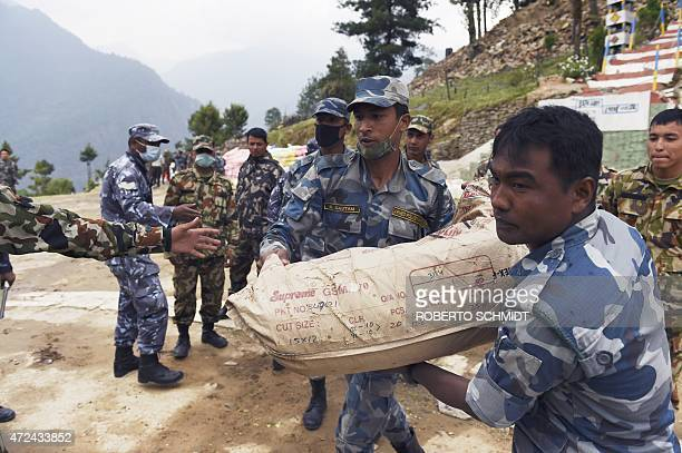Nepalese soldiers and policemen help loading food supplies into a Chinese transport helicopter during relief operations in the northcentral village...