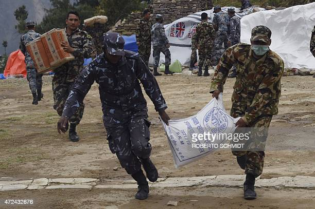 Nepalese soldiers and policemen run with parcels of food aid to load them on a Chinese helicopter during relief operations in the northcentral...