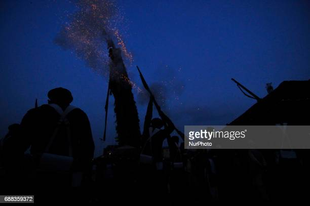 Nepalese soldiers fire a gun while priests carry the small chariot of idol Rato Machindranath towards the Bungamati after the celebration of Bhoto...