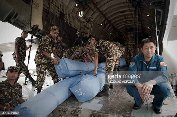 Nepalese soldiers unload rescue material from a Chinese air force cargo plane as a Chinese air force officer looks on at Kathmandu airport following...