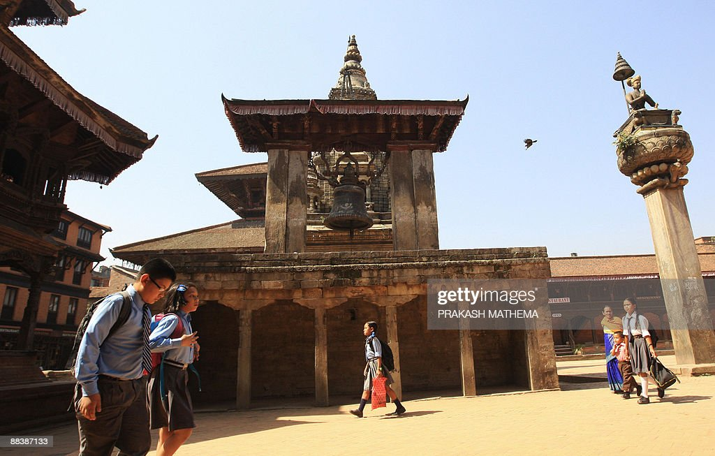 Nepalese students and pedestrians pass through the Bhaktapur Durbar Square in Bhakatpur some of 12 kilometers southeast of Kathmandu on June 10 2009...