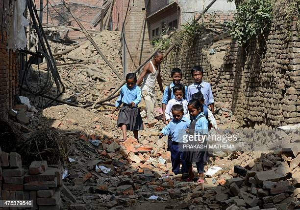 Nepalese students walk past damaged buildings to school in Bhaktapur on the outskirts of Kathmandu on May 31 2015 Schools are reopening in Nepal...