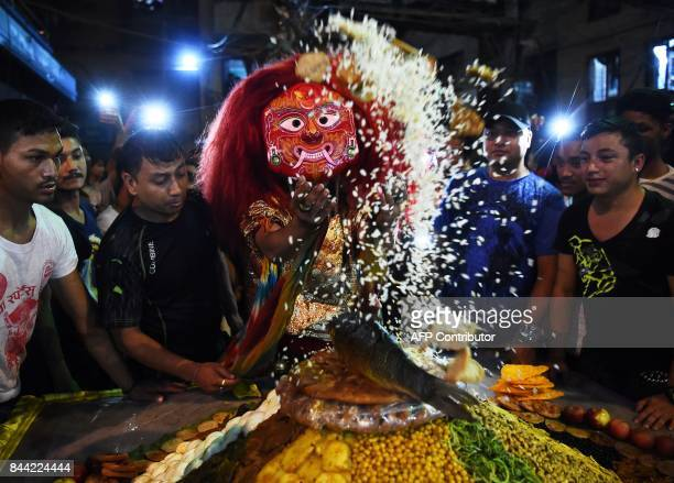 A Nepalese traditional masked 'Lakhe' dancer receives 'Samyabaji' on the sixth day of festivities at the Indra Jatra Festival in Kathmandu on...