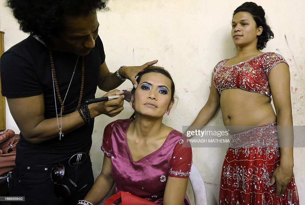 A Nepalese transgendered performer (C) has her make up put on backstage for an event on the International Day Against Homophobia and Trans-phobia in Kathmandu on May 17, 2013. Nepal, home to Asia's leading gay and transgender rights movement, legally recognizes a third gender category on documents for transgender people. AFP PHOTO/Prakash MATHEMA