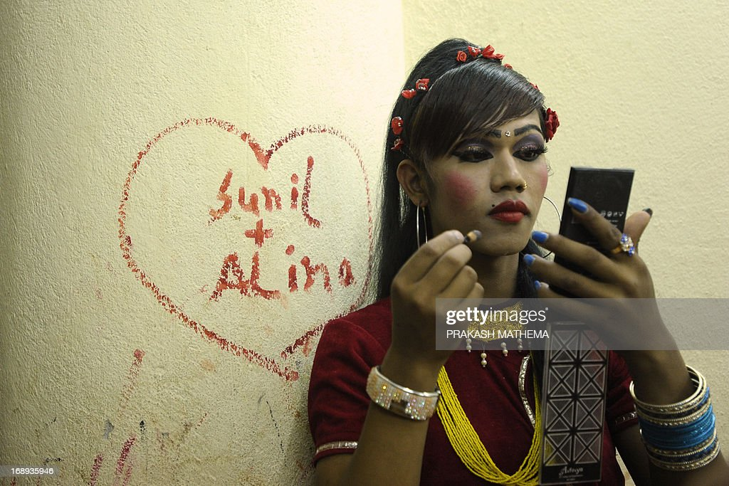 A Nepalese transgendered performer puts on make up backstage for an event on the International Day Against Homophobia and Trans-phobia in Kathmandu on May 17, 2013. Nepal, home to Asia's leading gay and transgender rights movement, legally recognizes a third gender category on documents for transgender people. AFP PHOTO/Prakash MATHEMA