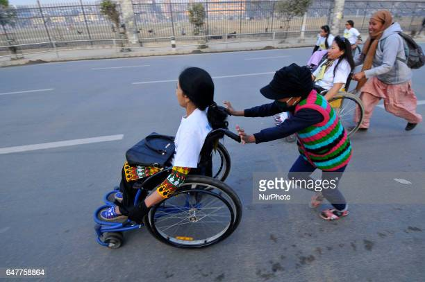 Nepalese wheelchair racer competing as help by their friends in the 1st Bodhisattvas In Action Wheelchair 4Km Marathon competition at Bhrikuti Mandap...