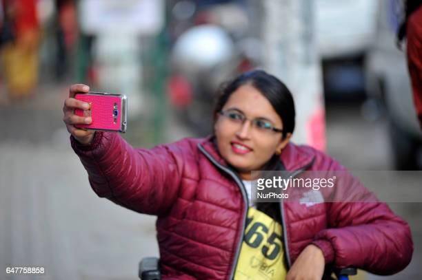 Nepalese wheelchair racer takes selfie from mobile as after participate in the 1st Bodhisattvas In Action Wheelchair 4Km Marathon competition at...