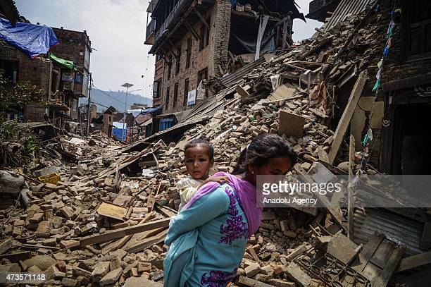 Nepalese woman carring her child walks past the collapse building in Sankhu village in Kathmandu Nepal on May 16 2015 following the second major...