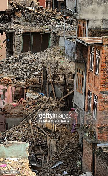 A Nepalese woman clears rubble of a collapsed house after an earthquake in Kathmandu on May 26 2015 The April 25 disaster was followed by another...