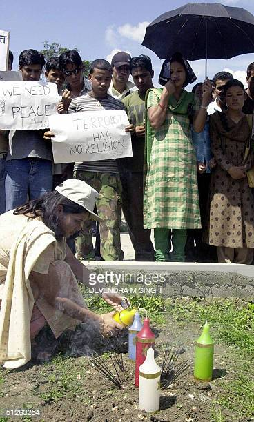 Nepalese woman lights a candle in memory of the 12 Nepalese hostages killed in Iraq as representatives from Nepal's Hindu Buddhist Muslim and...