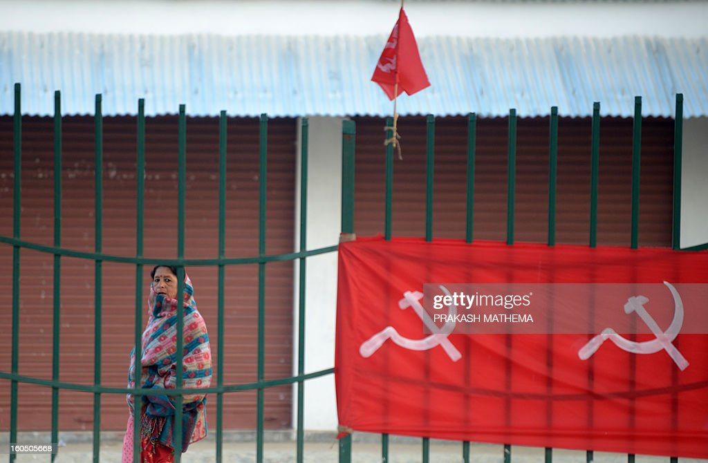 A Nepalese woman passes by flags for the inauguration of the Unified Communist Party of Nepal (Maoist) general convention in Hetauda, some 100 km south of Kathmandu on February 2, 2013. Thousands of Nepal's former rebel Maoists are due to gather for their biggest show of strength since taking up arms in a 10-year insurgency and toppling the world's last Hindu monarchy. AFP PHOTO/Prakash MATHEMA