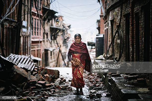 Nepalese woman walking through streets covered in the debris from fallen buildings on April 29 2015 in Kathmandu Nepal A major 78 earthquake hit...