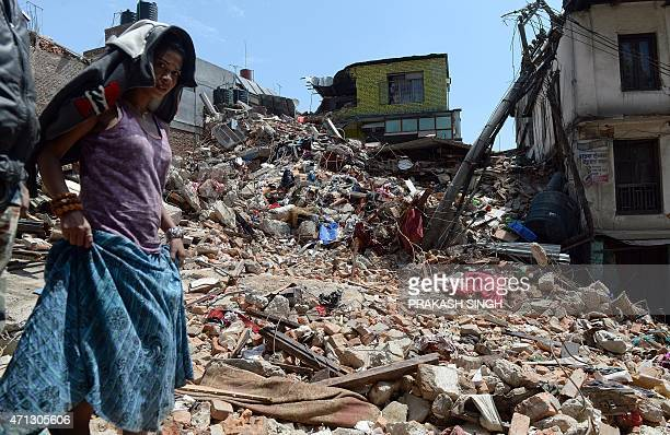 A Nepalese woman walks past a damaged house in Balaju in Kathmandu on April 27 2015 International aid groups and governments intensified efforts to...