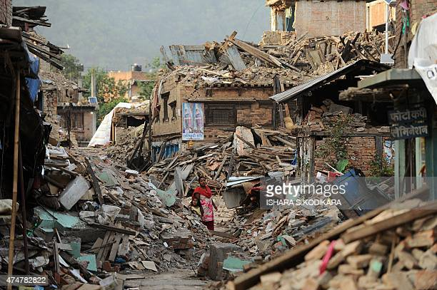 A Nepalese woman walks past damaged houses following an earthquake in Kathmandu on May 26 2015 The April 25 disaster was followed by another massive...