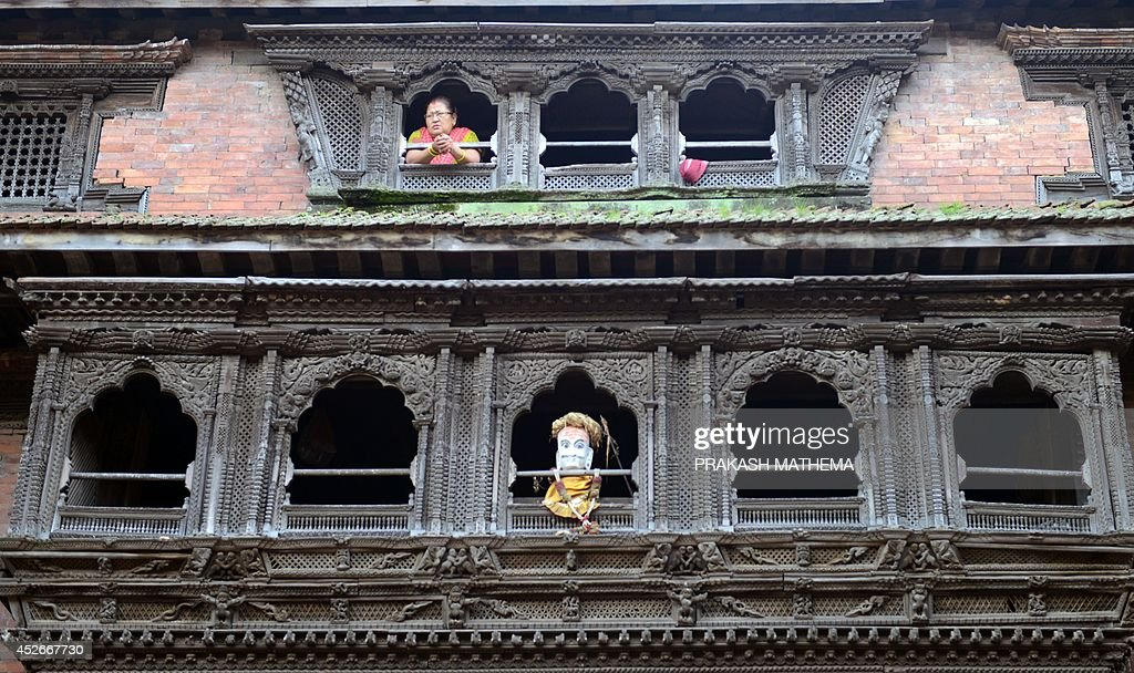 A Nepalese woman watches from her window during celebrations of the Hindu festival of 'Gathemangal' also known as Ghanta Karna in Bhaktapur on the...