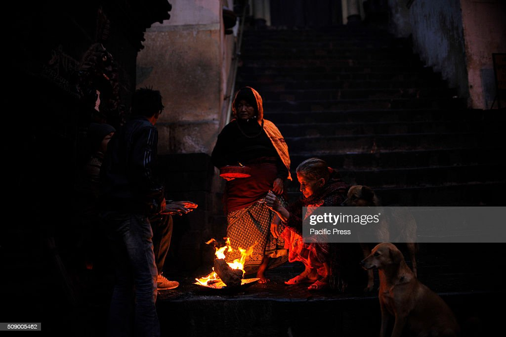 KATHMANDU, NEPAL, KATHMANDU, NP, NEPAL - : Nepalese women keep warm themselves by making bonfire in Pashupathnath Temple. Nepalese Hindu women fast and pray to Goddess Swasthani for Long life of their husbands and family prosperity during the month-long fasting festival celebration.