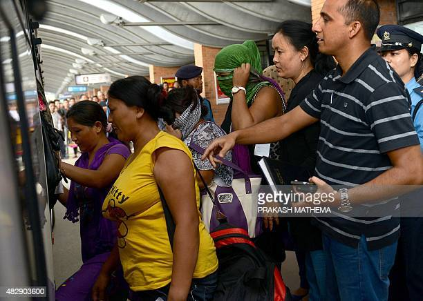 Nepalese women rescued from a suspected trafficking scheme in India board a bus on their arrival at Kathmandu's international airport on August 4...