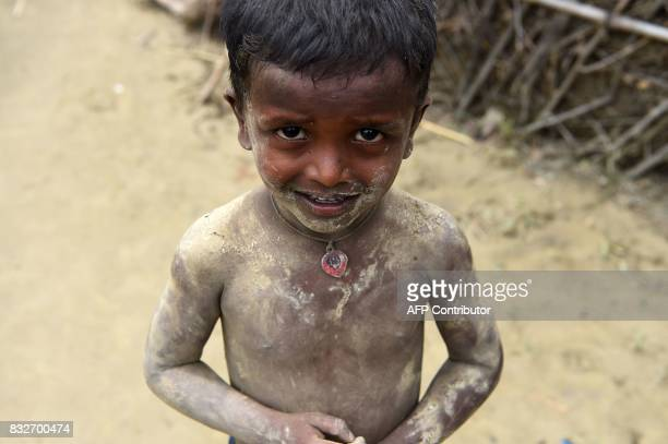 Nepali boy whose body is covered with mud looks on in his village on the outskirts of Biratnagar after the area was hit by flood some 240 kms from...