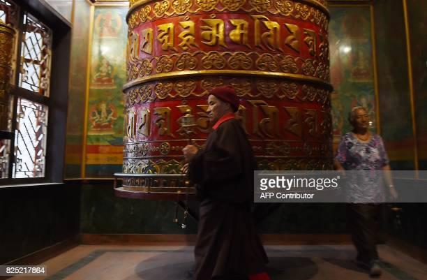Nepali Buddhist devotees spin a prayer wheel at the Boudhanath Stupa on the outskirts of Kathmandu on August 1 2017 Boudhanath Stupa was among...