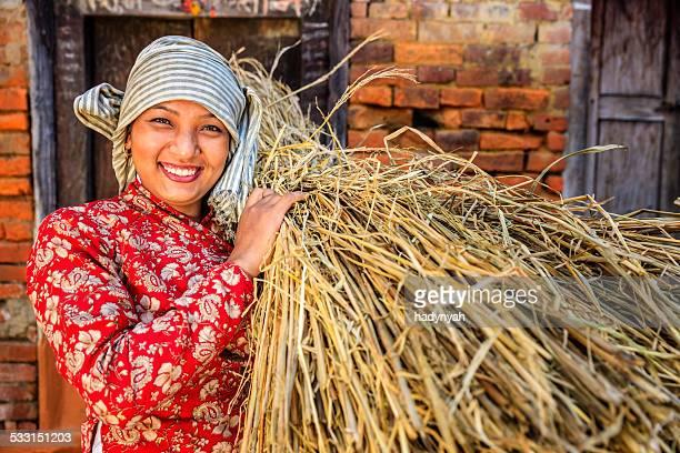 Nepali girl carrying rice straw in Bhaktapur, Nepal