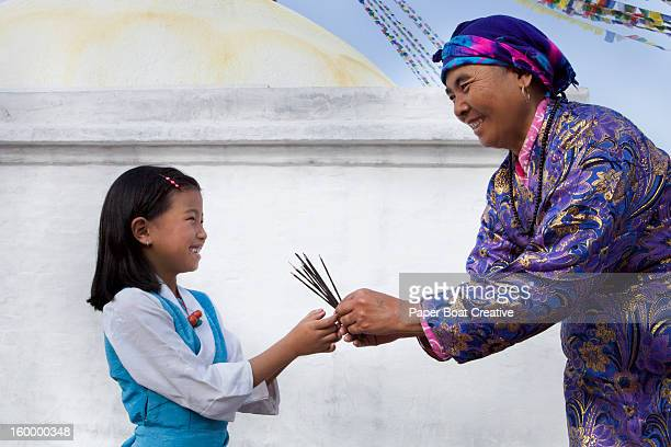Nepali grandmother giving incense to granddaughter