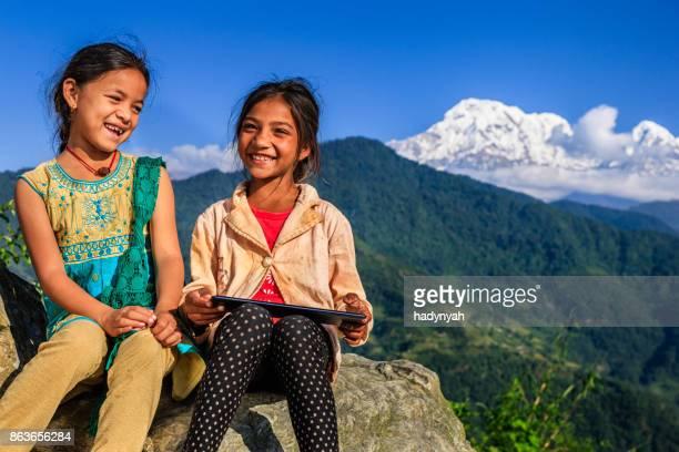 Nepali little girls using digital tablet, Annapurna Range on background