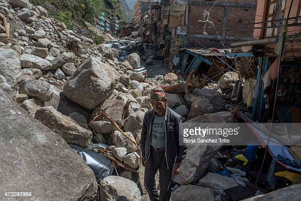 Nepali man of the walks through the rubble on May 2 2015 in Lipim Nepal The road from Bahrabise to Lipim the last Nepali village before the Tibetan...