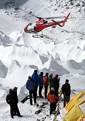 Nepali sherpas and other Nepali members of expeditons watch as a rescue helicopter takes off with the injured from Everest Base Camp on April 26 a...