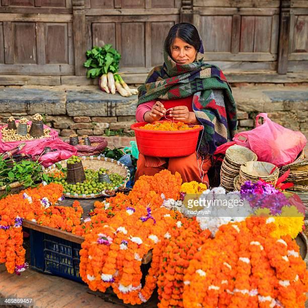 Nepali street seller selling flowers and vegetables in Patan, Nepal
