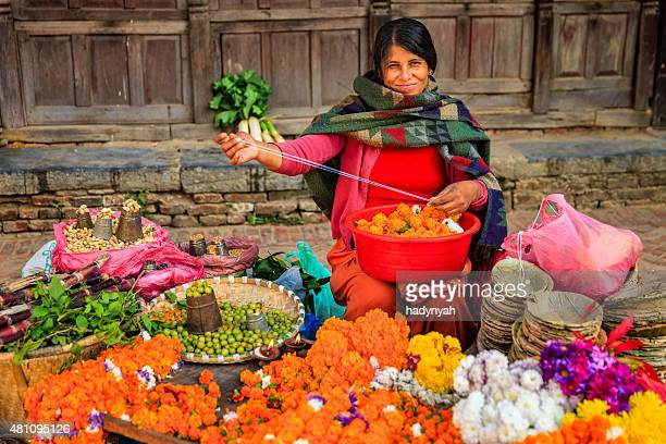 Nepali street Verkäufer Verkauf von Blumen und Gemüse in Patan, Nepal