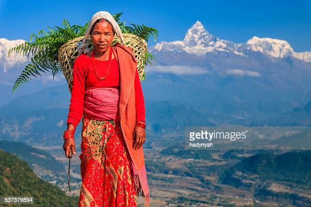 Nepali woman carrying basket, Machapuchare on background, Pokhara, Nepal