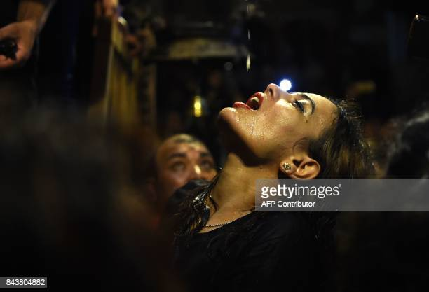 A Nepali woman drinks wine from a statue of Shwet Bhairav on the fifth day of the Indra Jatra festival on September 7 2017 in Kathmandu Nepal's...