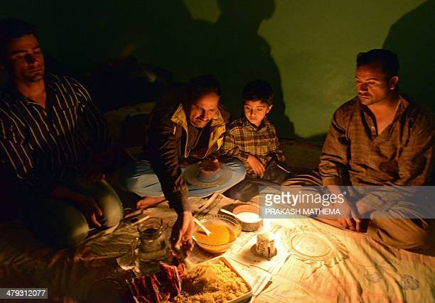NepalmigrationrefugeeFEATURE by Eric RANDOLPH This photo taken on March 13 2014 shows Pakistani refugee Nawid Ahmad and his family eating dinner by...