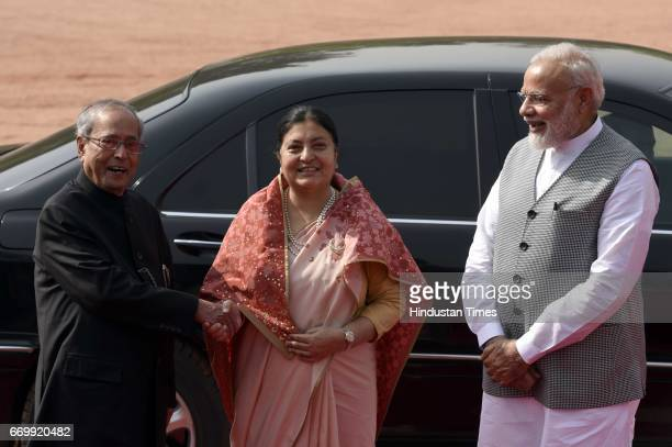 Nepal's Bidhya Devi Bhandari shakes hand with President of India Pranab Mukherjee as Prime Minister Narendra Modi looks on during a ceremonial...