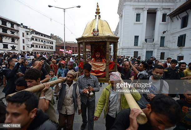 Nepal's Living Goddess the 'Kumari Devi' is carried by worshippers during a procession on the third day of the Seto Machindranath chariot festival in...
