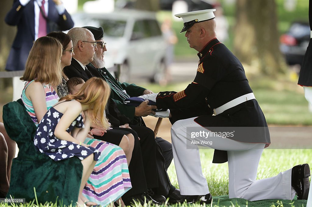 Nephew James C. Johnson (L) receives a flag from U.S. Marine Corps Command Sergeant Major Joseph Gray (R) during the burial of Private First Class James Bernard Johnson May 31, 2016 at Arlington National Cemetery in Arlington, Virginia. Johnson was assigned to Company K, 3rd Battalion, 8th Marines, 2nd Marine Division during WWII. He died sometime on the first day of battle against the Japanese, November 20, 1943, in an attempt to secure the small island of Betio in the Tarawa Atoll of the Gilbert Islands after landing.