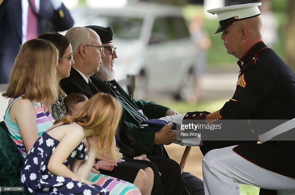 Nephew James C. Johnson (2nd R) receives a flag from U.S. Marine Corps Command Sergeant Major Joseph Gray (R) during the burial of Private First Class James Bernard Johnson May 31, 2016 at Arlington National Cemetery in Arlington, Virginia. Johnson was assigned to Company K, 3rd Battalion, 8th Marines, 2nd Marine Division during WWII. He died sometime on the first day of battle against the Japanese, November 20, 1943, in an attempt to secure the small island of Betio in the Tarawa Atoll of the Gilbert Islands after landing.