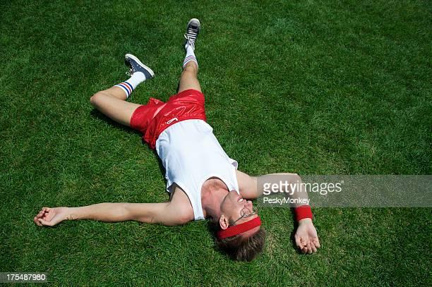 Nerd Athlete Lies Exhausted in Green Grass