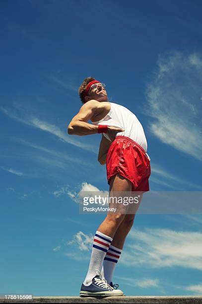 Grand dadais athlète se dresse contre le ciel bleu s'étirant