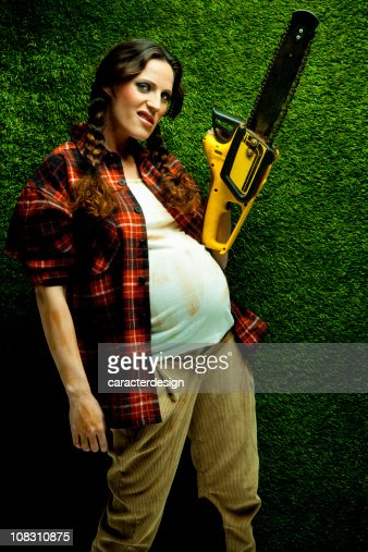 Nerd pregnant lumberjack holding a chainsaw : Stock Photo